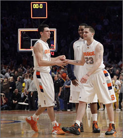 Syracuse's Eric Devendorf (23) is congratulated by teammates Andy Rautins, left and Kris Joseph after hitting a three-point basket from beyond half court at the buzzer at the end of the first half.