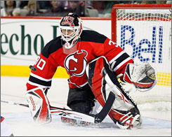 The Devils' Martin Brodeur won his 551st career game, tying Patrick Roy's NHL record for most victories by a goalie.