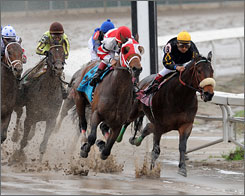 Friesan Fire and jockey Gabriel Saez, second from right, turns for home and surges ahead to win the Louisiana Derby horse race at a muddy Fair Grounds Race Course and Slots in New Orleans.
