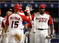 Puerto Rico's Carlos Delgado congratulates teammate Carlos Beltran after Beltran's solo home run in the seventh inning. Puerto Rico crushed the United States 11-1 in seven innings.