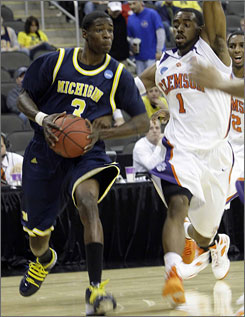 Michigan's Manny Harris, driving against Clemson's K.C. Rivers during the first half, scored 23 points to help the Wolverines win in their first NCAA tournament appearance in 11 years.