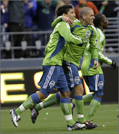 Fredy Montero, left, celebrates with Osvaldo Alonso, center, after his first goal.