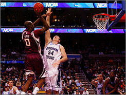 Texas A&M's Bryan Davis shoots over the defense of Chris Miles during the Aggies' first-round win.