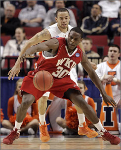 Illinois guard Calvin Brock and Western Kentucky forward Steffphon Pettigrew (30) battle for a loose ball in the first half of the Hilltoppers' upset of the Illini.