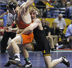 Iowa's Daniel Dennis, right, wrestles with Oklahoma State's Christopher Notte in a first-round bout in the 133-pound weight class. Dennis beat Notte 5-4.