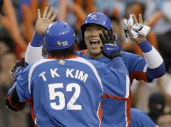 South Korea's Kim Tae-Kyun, left, is congratulated by teammate Kim Hyun-Soo after Tae-Kyun knocked out a two-run home run in the second inning in the team's victory over Venezuela.