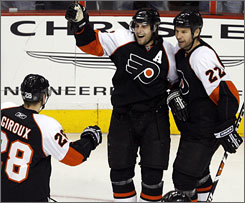 The Flyers' Simon Gagne, center, celebrates his third-period goal against the Devils with teammates Claude Giroux and Mike Knuble. Gagne's 30th goal of the season helped Philadelphia win its third straight game.