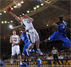 Luke Harangody, going up for a shot against Kentucky's Kevin Galloway, right, scored 30 points and grabbed 11 rebounds to help the Fighting Irish advance to New York and the NIT semifinals.