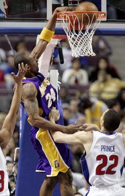 Los Angeles's Kobe Bryant dunks over the Pistons' Tayshuan Prince on the way to a 92-77 Laker victory.
