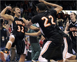 Tyler Evans, left, erupts after hitting a three-pointer at the buzzer to lift Findlay to the Division II national championship and a perfect season.