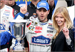 Jimmie Johnson celebrates with his wife, Chandra, in Martinsville Speedway's victory lane for the fifth time in the last six races at the Virginia short track.