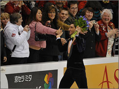 The USA's Evan Lysacek celebrates with the crowd after winning the gold in the World Figure Skating Championships.