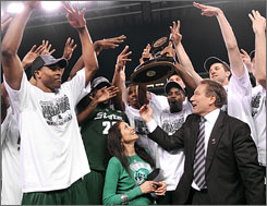 Michigan State coach Tom Izzo and his wife, Lupe, center, celebrate with players on the court after the Spartans stunned top-seeded Louisville to reach the Final Four in Detroit, just 92 miles away from the team's East Lansing campus.