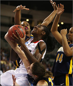 Connecticut's Tina Charles goes strong to the basket as three California players defend during the top-seeded Huskies' 77-53 victory on Sunday.