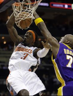 Charlotte Bobcats guard Gerald Wallace, left, dunks over Los Angeles Lakers forward Lamar Odom during the Bobcats' win on Tuesday night.