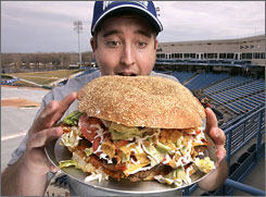 A West Michigan Whitecaps intern shows off the 4,800-calorie burger the team is offering this season.