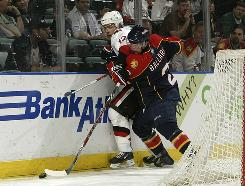 Panthers defenseman Keith Ballard slams Ottawa center Mike Fisher into the boards. Florida slammed the Senators 5-2. 