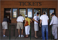 Fans purchase tickets to an exhibition baseball game between the Los Angeles Angels and the San Francisco Giants in Scottsdale, Ariz. As the economic downturn deepens, baseball officials report that ticket sales have decreased significantly.