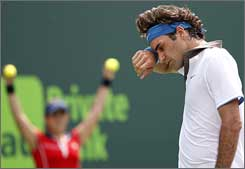 Roger Federer wipes his face during his Friday loss.