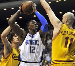 Magic center Dwight Howard goes against a double-team from the Cavaliers' Anderson Varejao, left, and Zydrunas Ilgauskas. Howard scored 20 points and grabbed 11 rebounds as Orlando handed Cleveland its worst loss of the season.