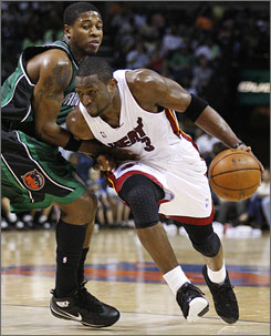 Heat guard Dwyane Wade drives by the Bobcats' Cartier Martin during their game in Charlotte. Wade registered a double-double as Miami clinched a playoff berth, one season after going 15-67.