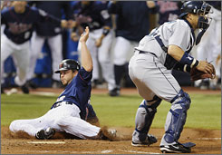 The Twins' Brian Buscher, left, slides home with the winning run behind Seattle Mariners catcher Kenji Johjima during the ninth inning of their game in Minneapolis. Minnesota won 6-5.