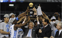 North Carolina coach Roy Williams, who didn't get a chance to shake hands with the Motown group The Temptations after it sang the national anthem Monday night, and his team raise the NCAA championship trophy after beating Michigan State.