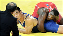 Dremiel Byers, right, wrestling China's Deli Liu in Beijing, will be seeking his eighth U.S. title in Las Vegas this week.