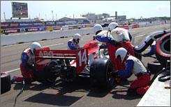 Vitor Meira comes to a halt for fresh tires and fuel on pit road at St. Petersburg, while the A.J. Foyt team's service is simultaneously broadcast on the big screen at left.