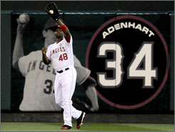 Angels outfielder Torii Hunter makes a catch in front of a tribute to Nick Adenhart on the outfield wall during the first inning.