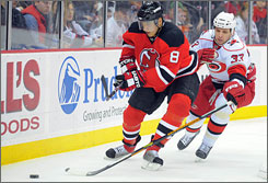 Devils left wing Dainius Zubrus, left, tries to keep position on Hurricanes defenseman Anton Babchuk during the second period.
