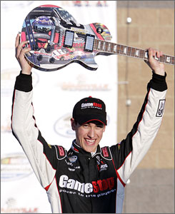 Joey Logano raises the championship guitar after winning the Pepsi 300 at Nashville Superspeedway. It was the second career win for the 18-year-old Logano.