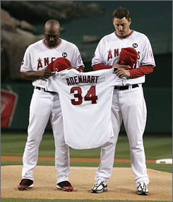 The Angels' Torii Hunter, left, and John Lackey hold the jersey of their late teammate, pitcher Nick Adenhart, during a moment of silence before Friday's game against the Boston Red Sox in Anaheim, Calif.
