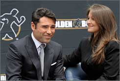 Oscar De La Hoya and his wife, Millie Corretjer, smile at his retirement announcement Tuesday in Los Angeles.