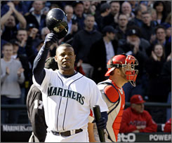 The Mariners' Ken Griffey Jr. tips his helmet while fans give him a standing ovation as he steps to the plate for his first at-bat against the Angels in the first inning.