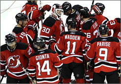Martin Brodeur is congratulated by his teammates after the New Jersey Devils defeated the Carolina Hurricanes 4-1 in the opening game of their playoff series in Newark on Wednesday night.
