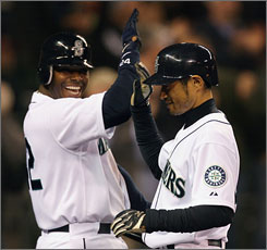 Seattle's Ichiro Suzuki, right, is congratulated by Ken Griffey Jr. after hitting a grand slam against the Los Angeles Angels. The hit tied Suzuki with Isao Harimoto, the all-time hits leader among Japanese players.