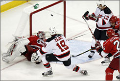 The Devils' Travis Zajac watches his shot fly past Hurricanes goalie Cam Ward for the game-winning goal in overtime, lifting New Jersey to the Game 3 victory and a 2-1 series lead.