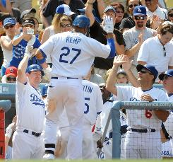 Matt Kemp celebrates his grand slam home run with manager Joe Torre. The homer was Kemp's first of two on the day, and the Dodgers went on to defeat the Rockies 14-2.