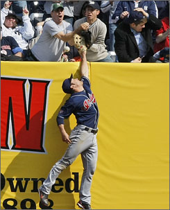 Fans try to catch Jorge Posada's seventh-inning, two-run home run as Indians right fielder Trevor Crowe leaps for the ball. The play was reviewed an upheld as a home run.