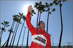Helio Castroneves waves to the crowd before practice sessions at the Grand Prix of Long Beach, one day after his acquittal on multiple tax evasion charges.