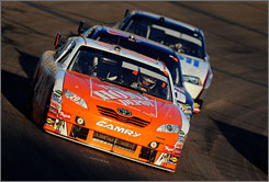 Joey Logano leads a pack in the late-afternoon sun at Phoenix International Raceway.