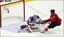 Washington right wing Matt Bradley scores past New York Rangers goalie Henrik Lundqvist, one of two goals Bradley scored during the first period.