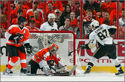 Sidney Crosby taps the puck past Flyers goalie Martin Biron to tie the game at 3 in the second period.