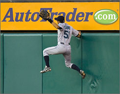 Seattle right fielder Ichiro Suzuki climbs the wall to go after a ball hit by the Angels' Gary Matthews Jr. in the third inning. After reviewing video, the umpires ruled fan interference and gave Matthews Jr. a ground rule double.