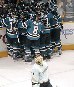 Sharks players mob Patrick Marleau as Ducks goalie Jonas Hiller leaves the ice. Marleau's second game-winning goal of the series came in overtime and helped San Jose stave off elimination.