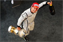 Jenson Button carries away the champagne and the trophy after netting his third win in four Formula One races this year.