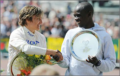 Germany's Irina Mikitenko shakes hands with Kenya's Sammy Wanjiru after receiving their trophies at the London Marathon.