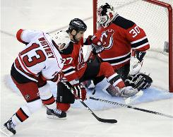 Carolina Hurricanes' Ray Whitney, left, scores a goal past New Jersey Devils' Mike Mottau and goaltender Martin Brodeur during the second period of Game 7.