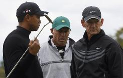 Tiger Woods talks with caddie Steve Williams and swing coach Hank Haney earlier this month at The Masters. Woods has denied rumors that he is unhappy with Haney and looking for a new swing coach,